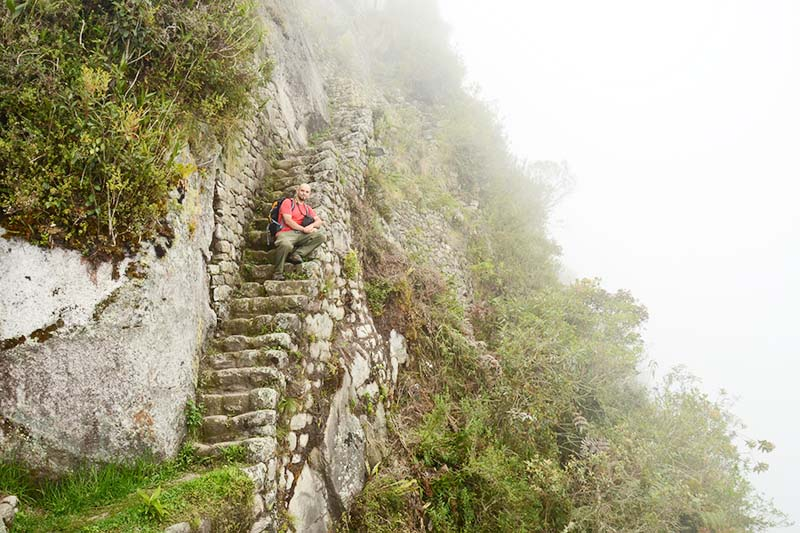 Tourist sitting on stairs of huayna picchu