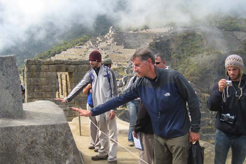 Tourists trying to feel the energy emitted by the Intihuatana in Machu Picchu