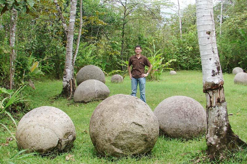 Turista junto a algunas esferas de piedra en Costa Rica