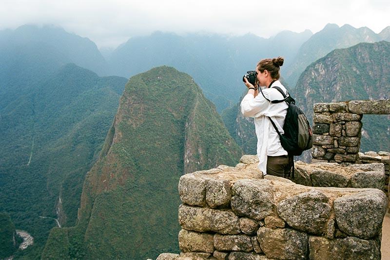 Turista tomando fotos en Machu Picchu
