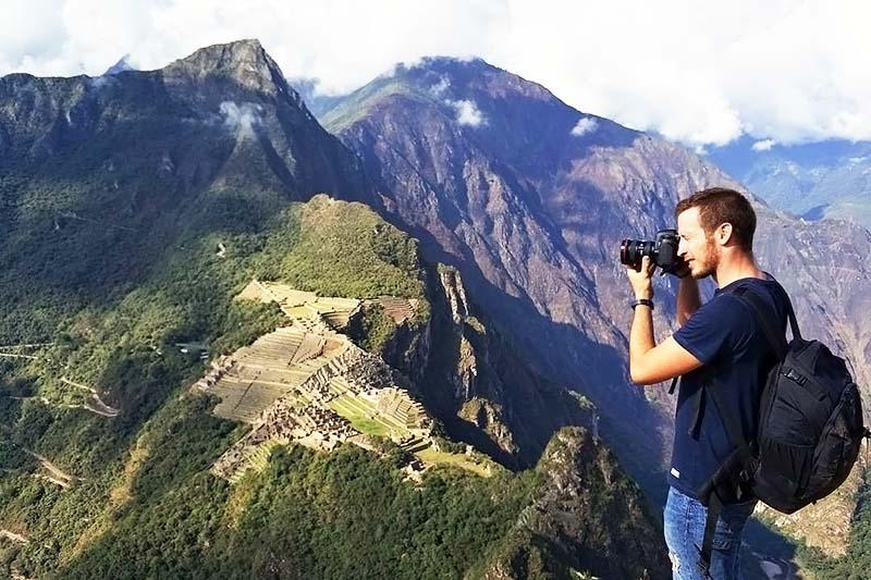 Turistas tomando fotografías en la cima de la montaña Huayna Picchu