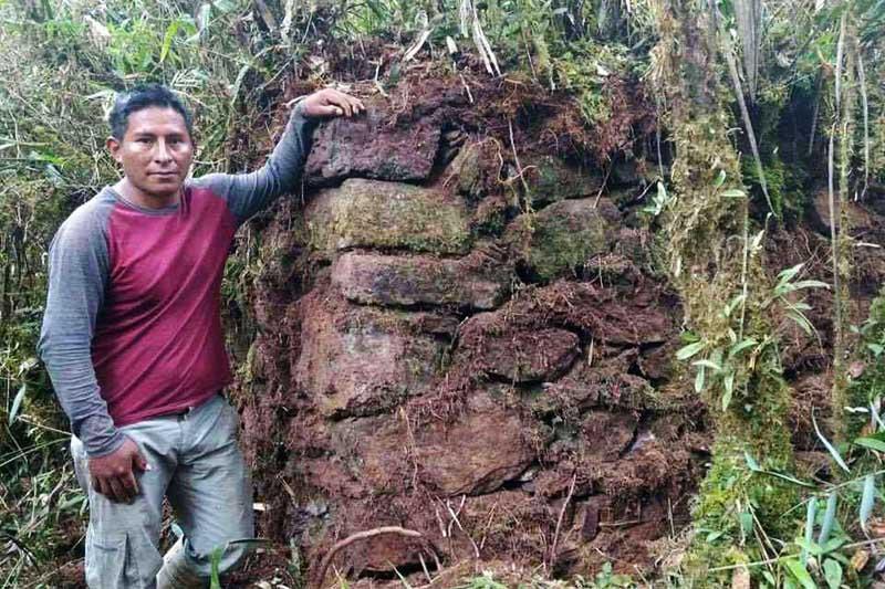 Poblador junto a muro de piedra descubierto