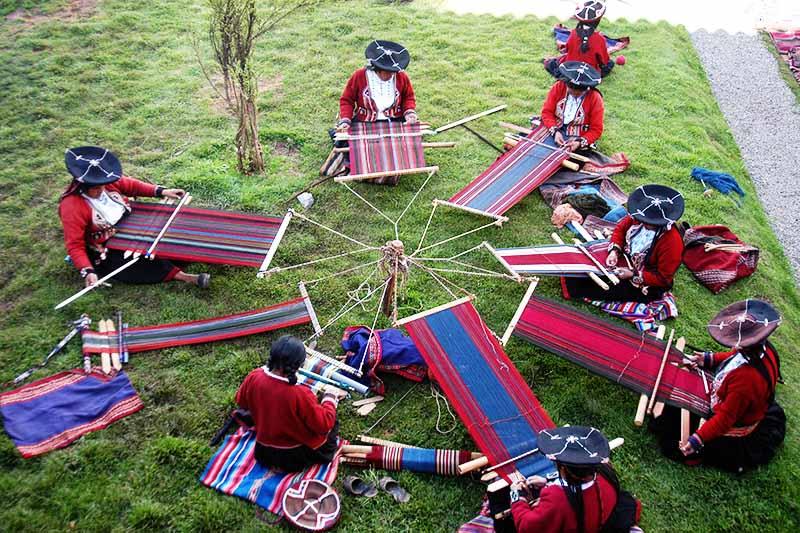 Varias mujeres de Chinchero haciendo el tejido de la lana