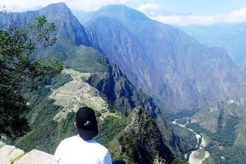 Turista observando Machu Picchu desde la cima de la montaña Huayna Picchu