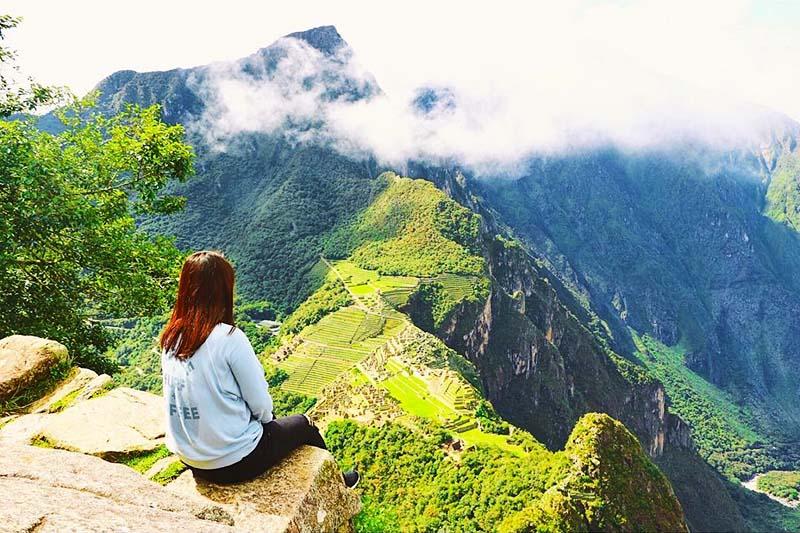 Turista mirando Machu Picchu desde la cima de la montaña Huayna Picchu
