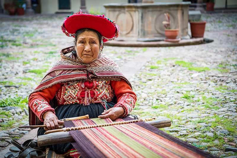 Mujer en pleno proceso del tejido de la lana en el interior del Museo Inka