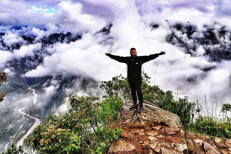 Turista entre las nubes en la montaña Machu Picchu