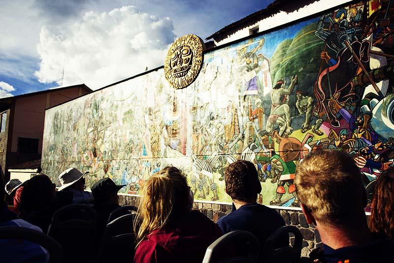 Turistas observando el mural de la historia del Cusco