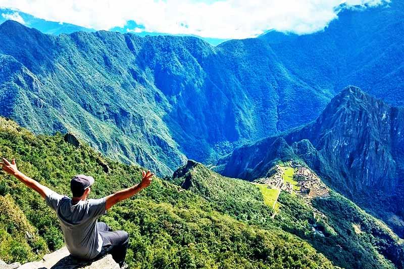 Turista en la cima de la montaña Machu Picchu