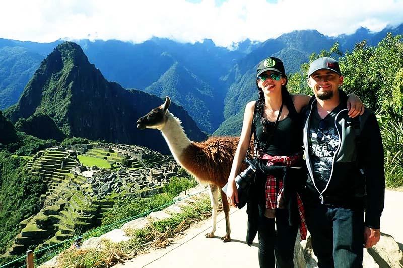 Turistas en Machu Picchu junto a una llama