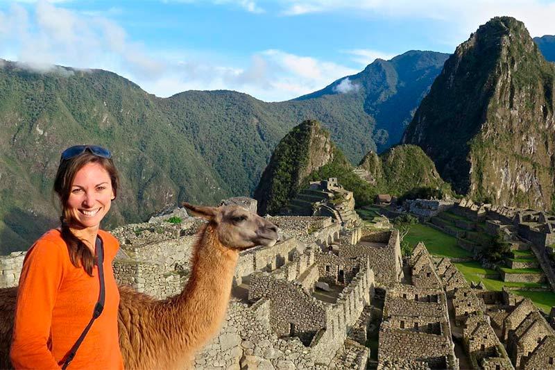 Turista con una llama en Machu Picchu